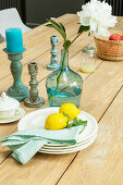 Lemons on stacked plates, peony in demijohn and vintage candlesticks on wooden table