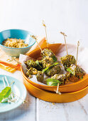 Ostrich meat skewers with lemon leaves, sesame seeds and bread crumbs