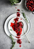 A rustic homemade cranberry suace spooned across a stack of plates with fresh rosemary and cranberries