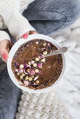 A woman holding a smoothie bowl with chocolate, dried roses and cocoa nibs