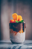 Chia pudding with fresh oranges, chocolate cream, mint and physalis