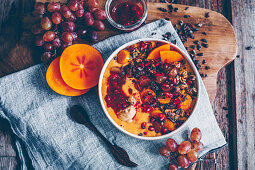 Smoothie bowl with kaki, papaya, pomegranate seeds, grapes, cacao nibs, raspberry compote, granola and physalis