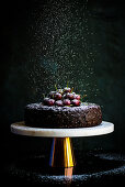 Vegan fruit cake decorated with cherries on a cake stand