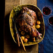 A roasted leg of lamb with herbs and apples