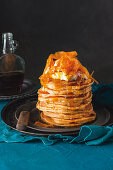 A stack of sweet potato pancakes with maple syrup