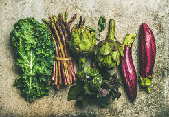 Green and purple fresh vegetables: Eggplans, green beans, kale, asparagus, artichoke, basil