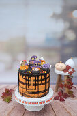 A Halloween drip cake with royal icing biscuits (made with Guinness, chocolate and blood orange)