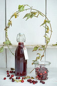 Cornelian cherry juice in a bottle, cornelian cherries in storage jar, and a cornel cherry branch
