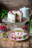 Cake with pistachio sponges, baked raspberry cheesecake layer and raspberry cream cheese