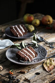 Slices of chocolate and pear cake on wooden table