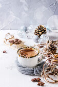 Vintage mug in wool scarf of hot chocolate, decor with nuts, caramel, spices