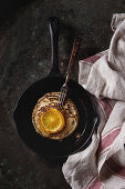Homemade pancakes with fried orange, served in cast-iron pan on kitchen towel over dark old rusty background