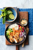 A salad bowl with pork sate, rice noodles and vegetables (Asia)