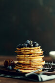 A stack of pancakes with blueberries and maple syrup