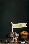 Chocolate muffins with paper flags against a dark background