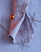 Christmas arrangement of linen napkin, silver stars and copper-coloured bauble