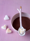 Marshmallow hearts decorated with gold beads, served with hot chocolate