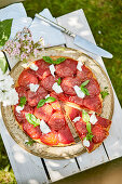 Summery tomato tart outdoors on a wooden box