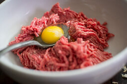 Ingredients for meatball: minced meat and egg yolk in a bowl