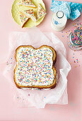 A fairy bread cake with buttercream and sugar sprinkles