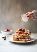 A woman pouring syrup over French toast with cranberries and quark
