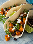 Soft taco shells with sweet potatoes, beans and rocket