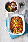 Gnocchi and chicken gratin with a cheese crust and winter vegetable salad