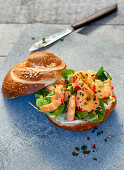 A lye bread roll with chili prawns and chives