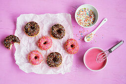 Mini doughnuts with chocolate, icing and sugar sprinkles on paper