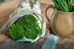 Chives wrapped in a towel on a wooden board