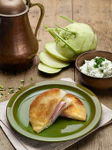 Breaded cabbage slices stuffed with ham and cheese, served with chive cream