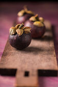 Mangosteens on a wooden board