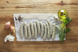 Raw sausages with ingredients on paper