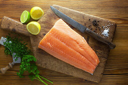 Side of raw salmon with ingredients on a wooden board