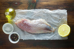 Raw red snapper with ingredients on a wooden surface