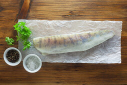 Raw zander with ingredients on a piece of paper