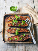 Glazed miso aubergines on a baking sheet with sesame and cilantro