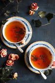Two cups of tea decorated with roses