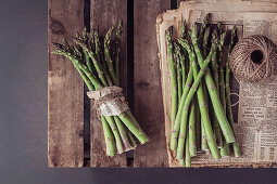 Green asparagus and newspaper on a wooden pallet
