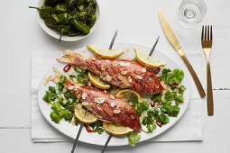 Grilled red snapper with lemons and flaked almonds on skewers