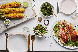 Grilled red snapper with corn cobs and a vegetable salad