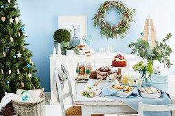 Weihnachtsbuffet in pastellblauem Raum mit Christbaum