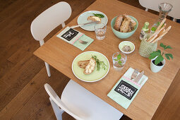 Cutlery pouches with name tags on table set with mint-green crockery