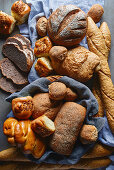 Breakfast breads and pastries in a bread basket and on a cloth