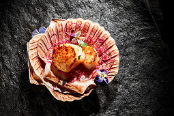 Fried scallops with edible flowers in mussel shells