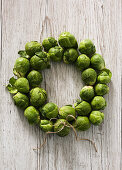 A wreath of brussels sprouts on a white wooden background