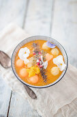 A smoothie bowl with cantaloupe melon, pineapple and coconut chips