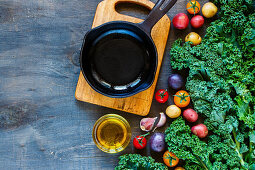 Vintage cast iron skillet and fresh colorful organic vegetables for healthy eating on rustic wooden background