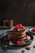 Chocolate pancakes with chocolate sauce, sliced bananas ad raspberries