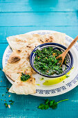 Crisp flatbread with Zhug sauce (spicy sauce with coriander and parsley, Yemen)